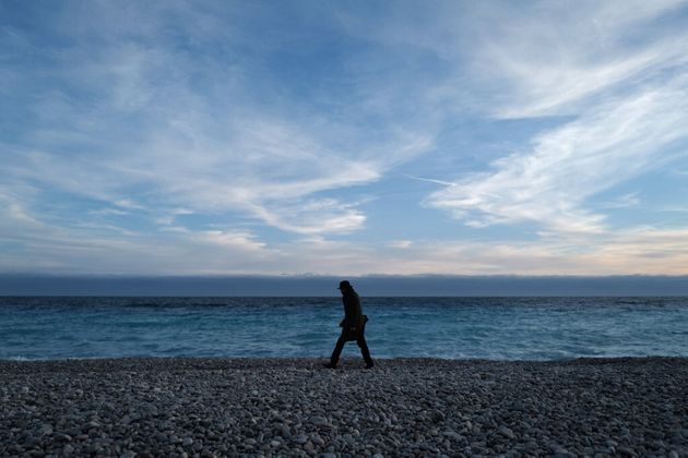 Un homme marche sur une plage de Nice le 16 février