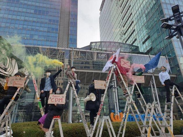 """서울 강남구 포스코센터 앞에서 시민단체들이 사다리 위에 올라가 연막탄을 터뜨리며 """"포스코는 반성하고 미얀마에 사과하라""""고 구호를 외치고 있다. 전광준"""