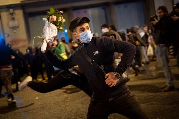 Un joven lanza un ramo de flores contra la policía, anoche, en
