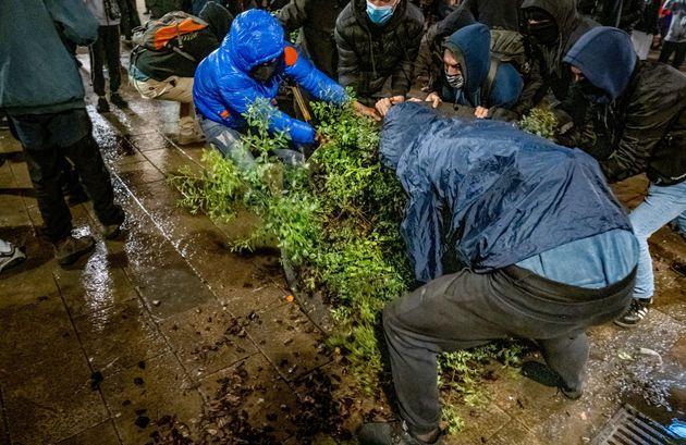 Un grupo de manifestantes mueve una jardinera para montar una barricada durante las protestas por el...