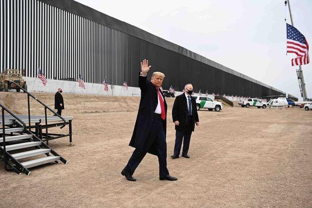 Donald Trump saluda a la prensa desde uno de los tramos de su muro fronterizo, en