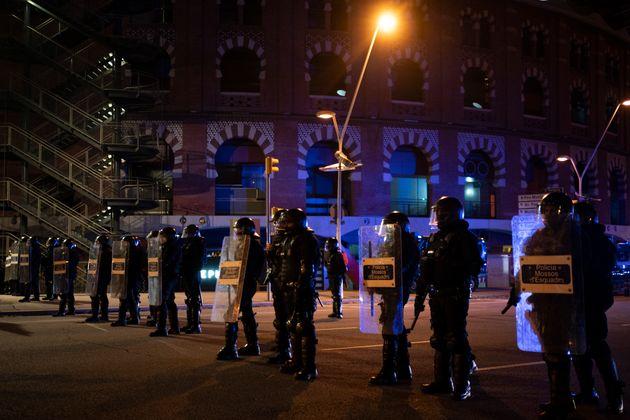 Agentes de la policía catalana bloquean una calle durante una protesta contra la detención del cantante...