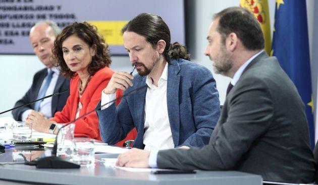Pablo Iglesias escucha a José Luis Ábalos, en una rueda de prensa tras un Consejo de