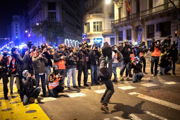Un grupo de fotógrafos toma imágenes de un hombre que arroja una botella contra una comisaría de policía...