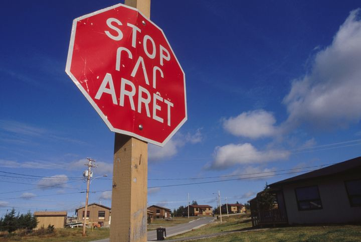 A stop sign in English, French and Cree languages.