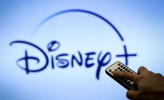 A hand holds a remote control in front of a screen with the Disney Plus logo on