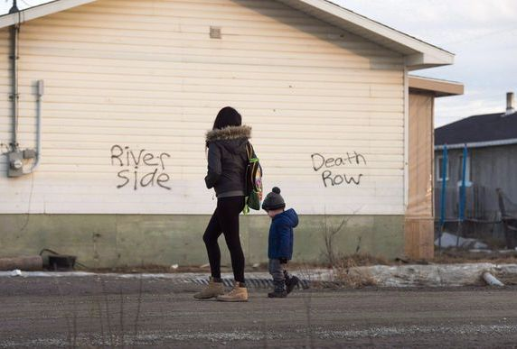 A woman and a child walk through the streets in Attawapiskat, Ont., on April 16, 2016. Jordan's...