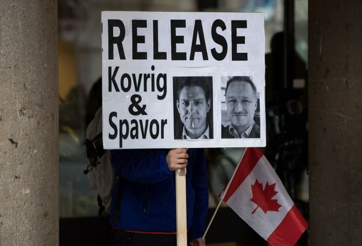 A young man holds a sign bearing photographs of Michael Kovrig and Michael Spavor outside B.C. Supreme Court where Huawei chief financial officer Meng Wanzhou was attending a hearing, in Vancouver on Jan. 21, 2020.