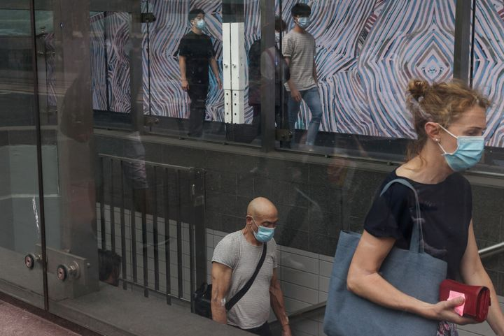 Commuters wearing protective face masks in accordance with new public health regulations for riding public transit depart a train station in the wake of a coronavirus disease (COVID-19) outbreak in Sydney, Australia.