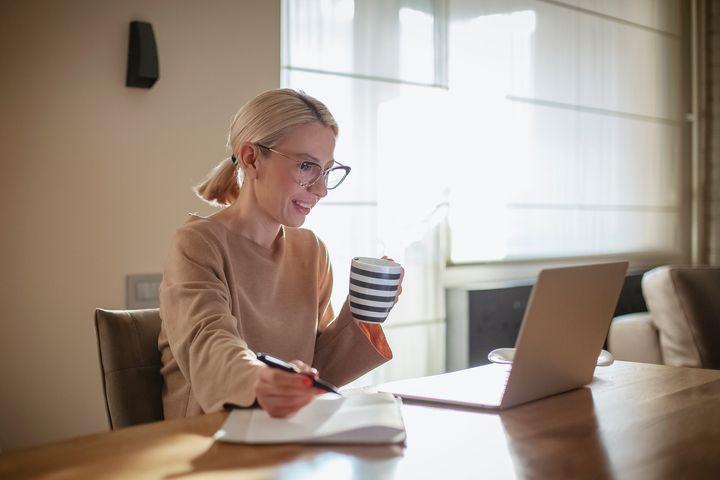 Γυναίκα δουλεύει πίνοντας τον καφέ της