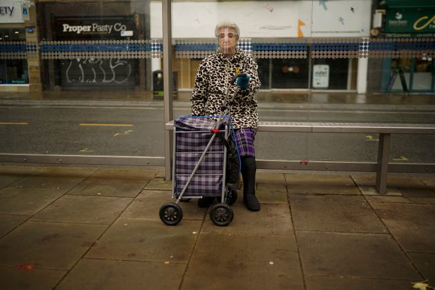A woman wears a face shield as she sits at a bus stop in Sheffield last