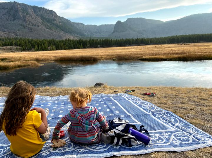The author's daughters enjoying a picnic along the Firehole River in Yellowstone National Park in October 2020.