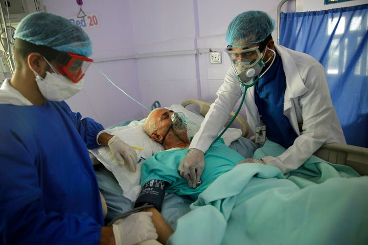 Medical workers attend to a COVID-19 patient in an intensive care unit at a hospital in Sanaa, Yemen, on June 14, 2020.