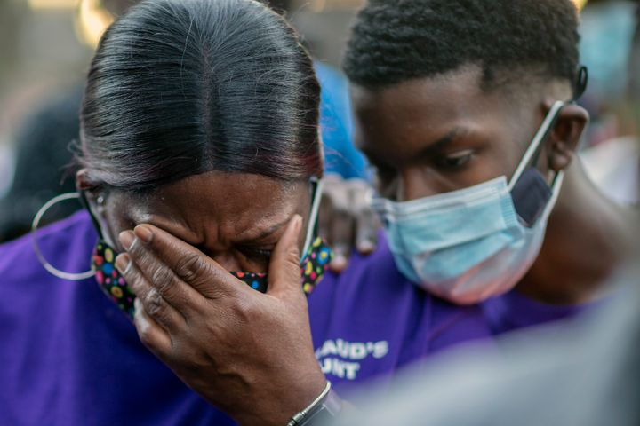 Evon Arbery, Ahmaud Arbery's aunt, is comforted by a family member during Tuesday's memorial walk and candlelight vigil.