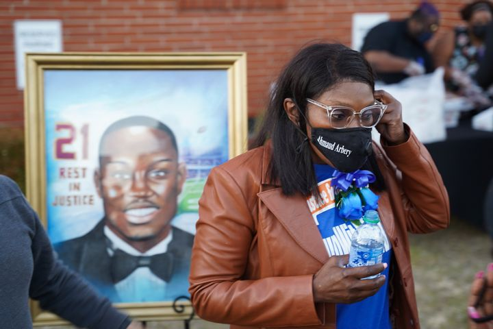 Wanda Cooper-Jones, the mother of Ahmaud Arbery, stands in front of a painting of her son after a candlelight vigil for him on Tuesday at the New Springfield Baptist Church in Waynesboro, Georgia. Arbery was shot and killed while jogging near Brunswick, Georgia, a year ago on Tuesday after being chased by two white men.