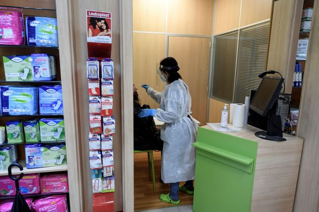 Una farmacéutica realiza una prueba de antígenos en una farmacia de