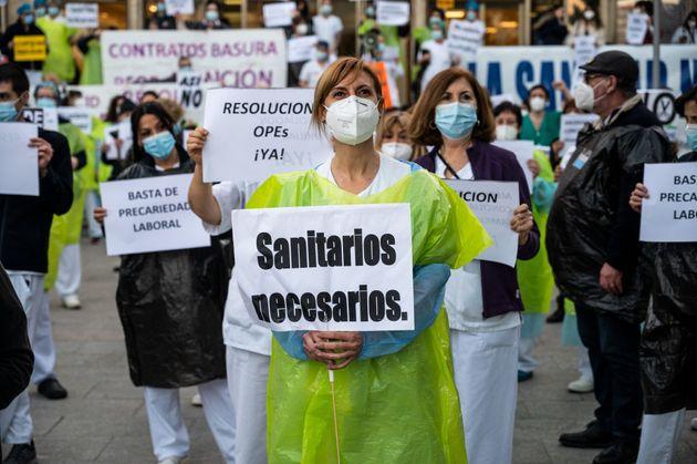 Trabajadores de la salud protestando con pancartas contra la precariedad frente al Hospital 12 de Octubre...