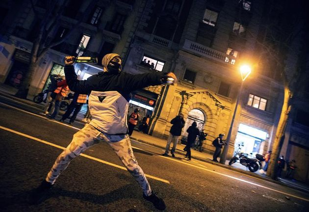 Un manifestante se dispone a lanzar una botella a la policía durante la protesta contra la detención...