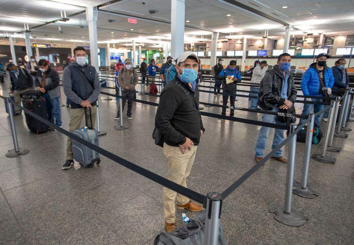 Des travailleurs mexicains maintiennent la distanciation à leur arrivée à l'aéroport Trudeau avant d'être conduits vers les fermes du Québec, le mardi 14 avril 2020.