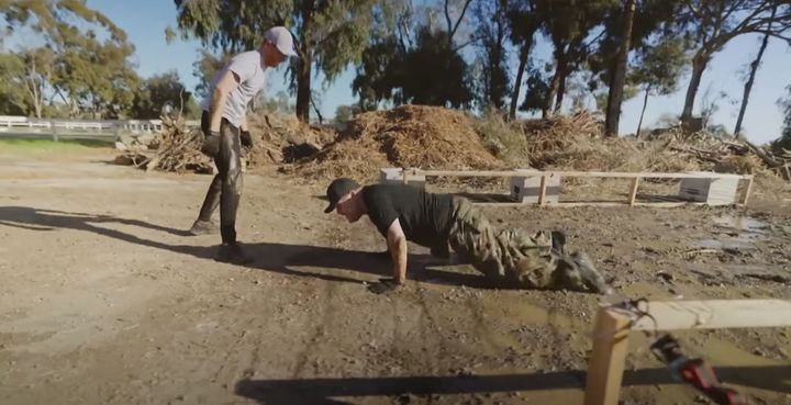 James Corden hams up his repulsion during the mud crawl exercise.