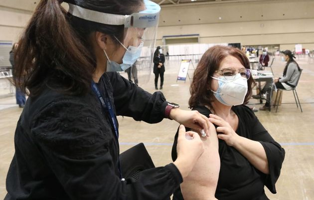 A woman wearing a face mask receives a dose of COVID-19 vaccine at a COVID-19 immunization clinic at the Metro Toronto Convention Centre in Toronto on Jan. 18, 2021..