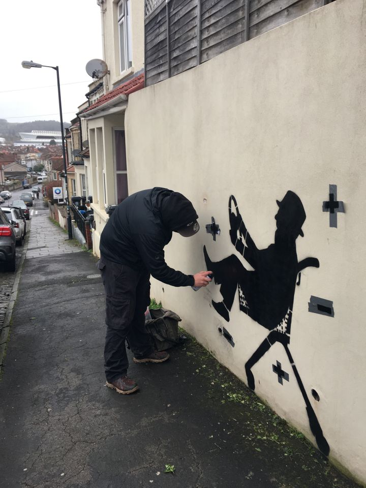 Street artist DIFF pictured painting his tribute to his father and the coronavirus vaccine in Bristol, England.