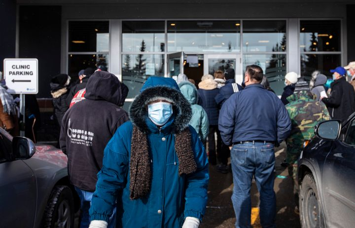 People line up outside a vaccine clinic as seniors wait to get the COVID-19 vaccine in Edmonton on Friday.