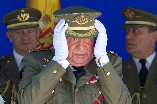 El rey Juan Carlos, con las manos en la cabeza, durante un acto en