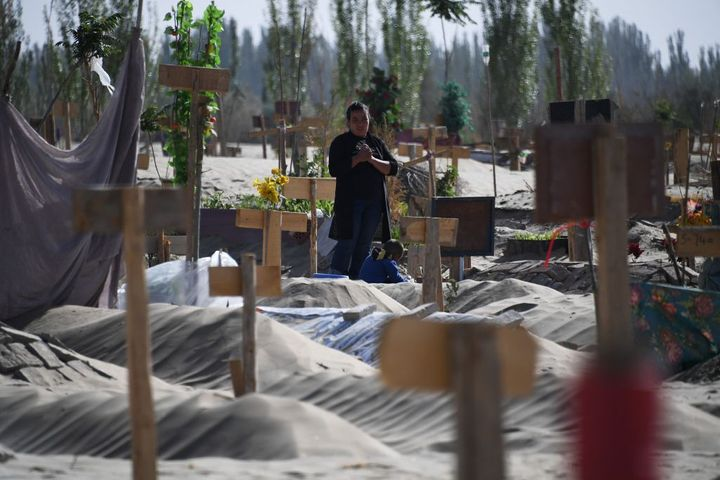 This photo taken on May 31, 2019, shows a woman in a Uighur graveyard on the outskirts of Hotan in China's northwest Xinjiang