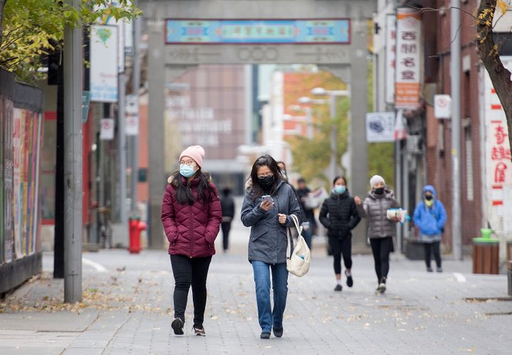 People make their way along a street in Montreal's Chinatown.