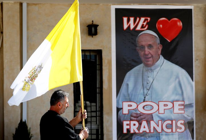A priest holds a Vatican flag as he walks by a poster of Pope Francis during preparations for the Pope's visit in Mar Youssif