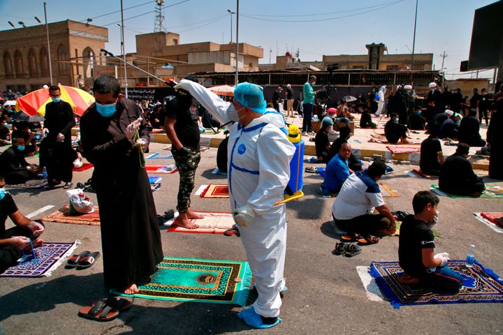 A volunteer sprays disinfectant as a precaution against the coronavirus during Friday prayers in Baghdad, Iraq, on Sept. 11,
