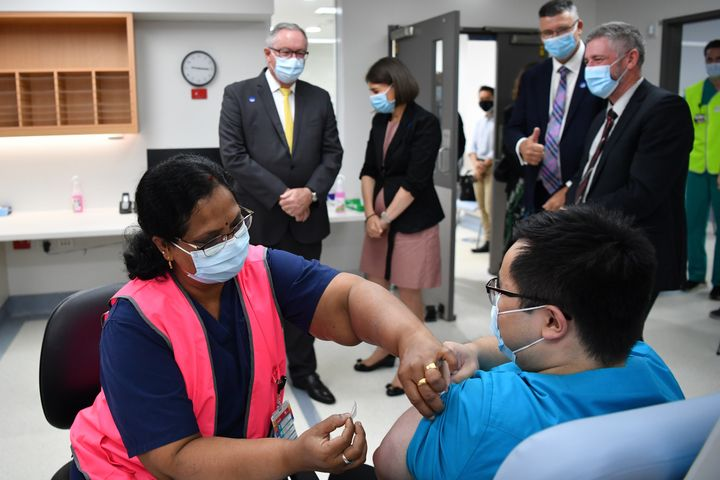 NSW Health Minister Brad Hazzard, left, and Premier Gladys Berejiklian look on Monday as NSW Health worker Andrew Santoso, a radiographer, receives his COVID-19 vaccination at Westmead Hospital.