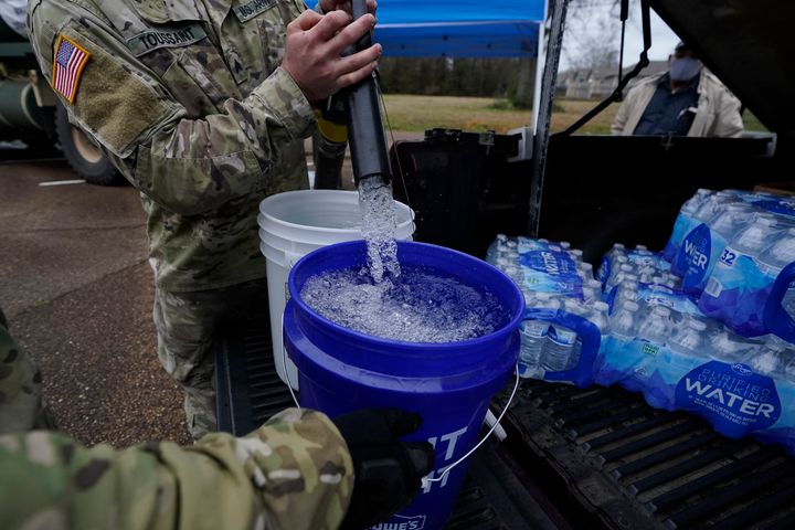 Mississippi Army National Guard Sgt. Chase Toussaint fills five-gallon buckets with nonpotable water at the New Mt. Zion Miss