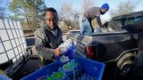 Lamar Jackson, left, stacks bottled water brought by Mac Epps of Mississippi Move at a senior residence in Jackson, Mississippi, on Feb. 22, 2021. Rising temperatures have melted the snow and ice in Mississippi, but tens of thousands of people still had little or no water service.