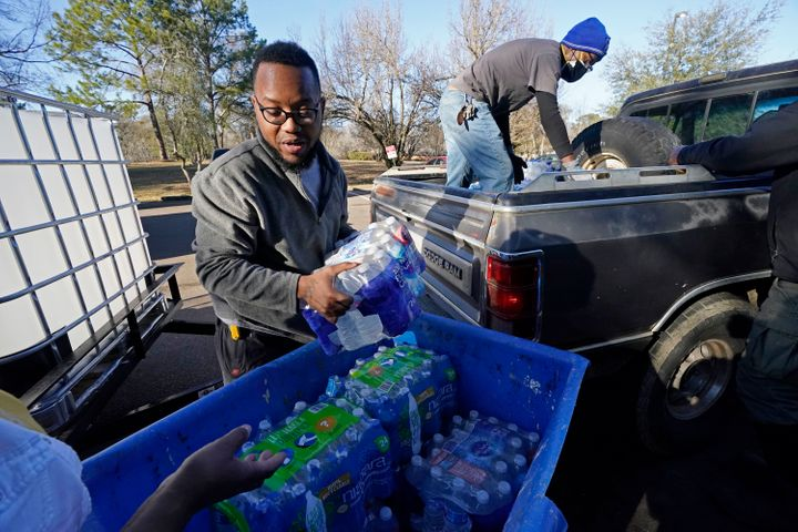 Lamar Jackson, left, stacks bottled water brought by Mac Epps of Mississippi Move at a senior residence in Jackson, Mississip