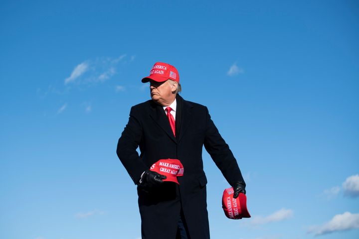 Trump, himself wearing a MAGA hat, throws some of them to his listeners at a rally for his reelection bid in Avoca, Pennsylvania on Nov. 2, 2020.