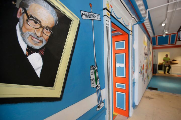 A mural that features Theodor Seuss Geisel, left, also known by his pen name Dr. Seuss, covers part of a wall near an entrance at The Amazing World of Dr. Seuss Museum, in Springfield, Mass., seen on May 4, 2017.
