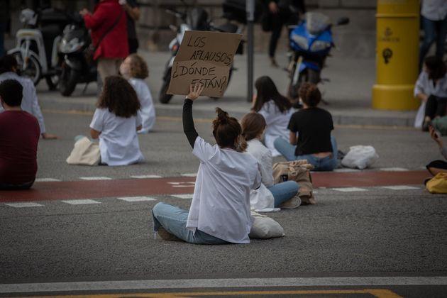 Una profesional sanitaria sostiene un cartel en una concentración de Médicos Internos Residentes (MIR)...