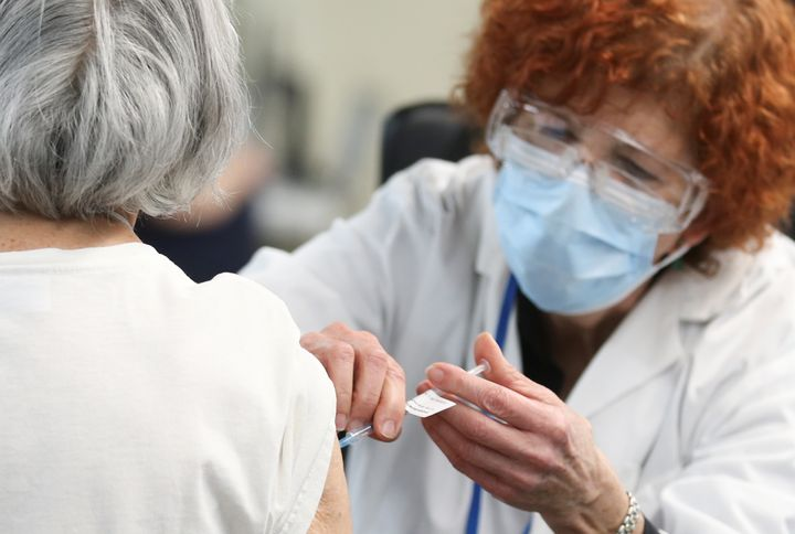 A woman is vaccinated at Olympic Stadium in Montreal on Monday. Canadians on the coasts and Quebec were most optimistic about their provinces rollout plans, according to a survey.