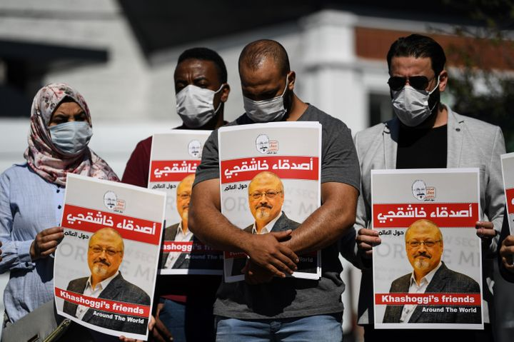 People hold posters bearing Khashoggi's picture at an Oct. 2, 2020, event marking the second-year anniversary of his death.