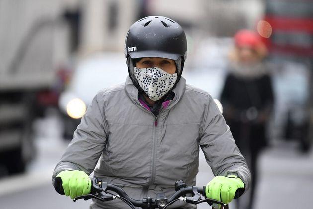 Une cycliste porte un masque en circulant dans Londres le 2 mars 2020 (photo