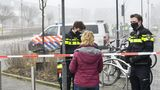 Police officers speak with a pedestrian as they close off a street after an explosion occurred near a Covid-19 test centre, shattering windows but causing no apparent injuries, in Bovenkarspel, the Netherlands, on March 3, 2021.