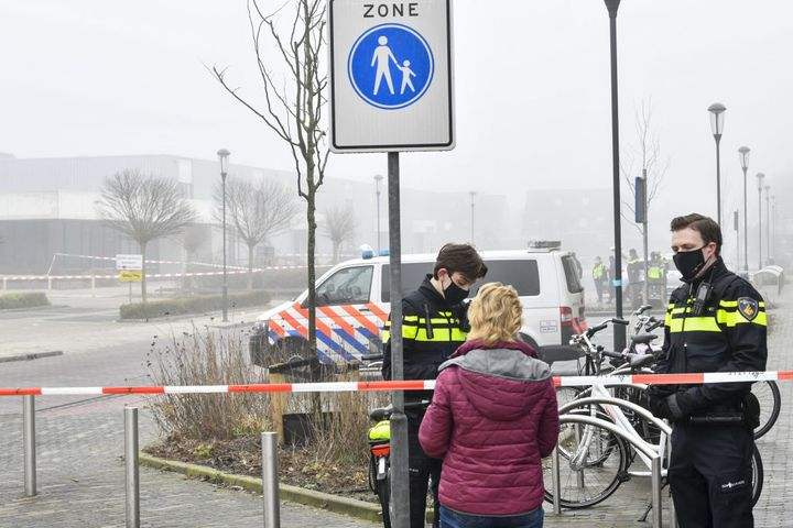 Police officers speak with a pedestrian as they close off a street after an explosion occurred near a Covid-19 test centre, s