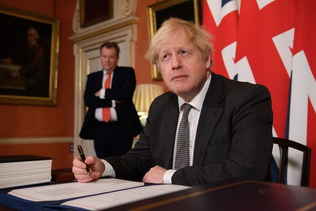 Boris Johnson poses for photographs after signing the trade and cooperation agreement between the UK...