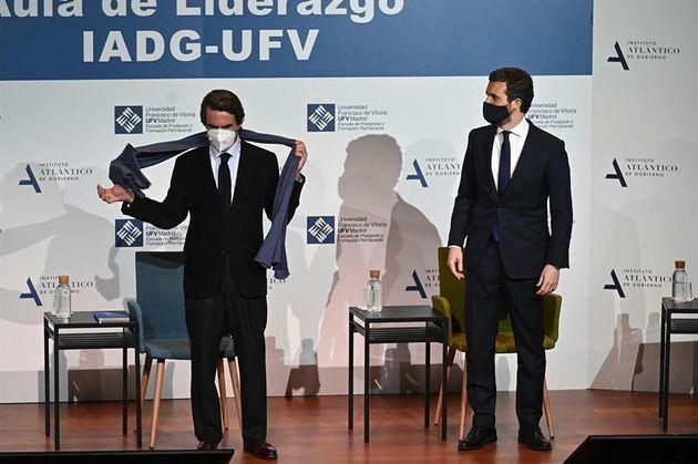 El expresidente del Gobierno, José María Aznar, se quita la bufanda bajo la atenta mirada del presidente...