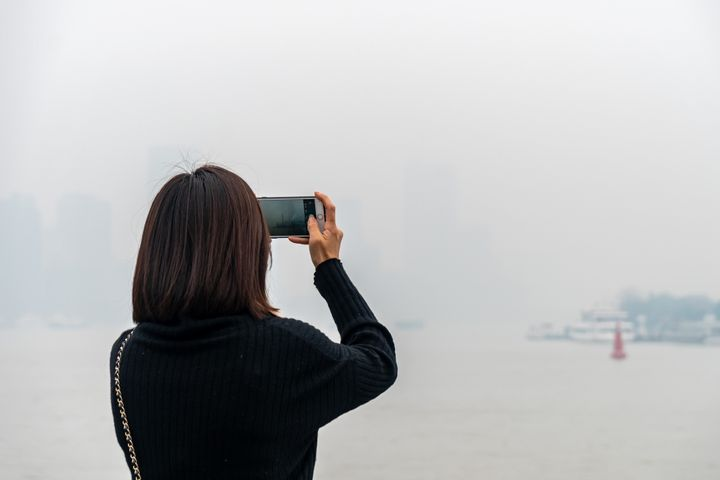 A tourist takes photos of the haze in Shanghai, China, on Dec. 24, 2020.