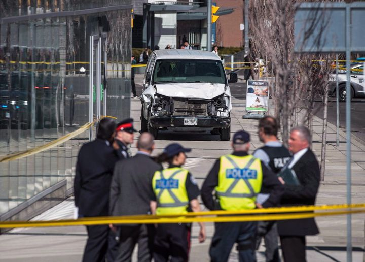 Police are seen near a damaged van in Toronto after several pedestrians were hit with a vehicle on a sidewalk on April 23, 2018. The deliberate attack left 10 people dead and 16 injured.