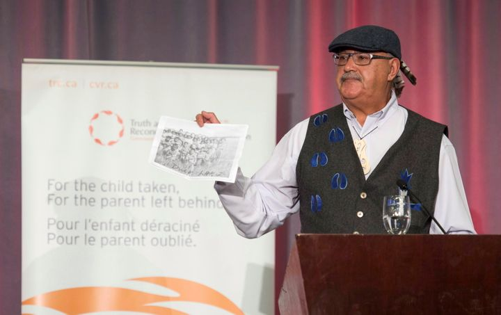 Residential school survivor Eugene Arcand holds up a picture of his classmates at the release of the final report of the Truth and Reconciliation commission on Dec. 15, 2015.