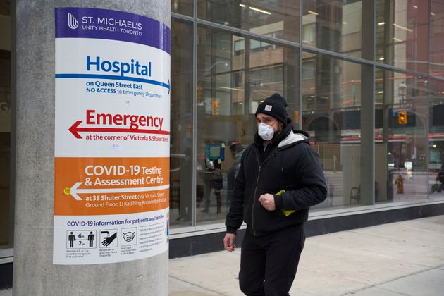 A man wearing a protective face mask walks past St. Michael's Hospital in Toronto on Jan. 11, 2021, amid...